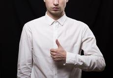 Ritratto di un giovane in una camicia bianca su un fondo nero Fotografia Stock Libera da Diritti