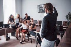 Ritratto di un gruppo creativo felice della gente che parla nell'ufficio alla riunione immagini stock libere da diritti
