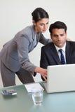 Ritratto di un gruppo messo a fuoco di affari che lavora con un computer portatile Immagine Stock