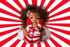 Ritratto di un'indicazione allegra prescolare della ragazza del bambino Colpo dello studio Fondo rosso e bianco della banda fotografia stock