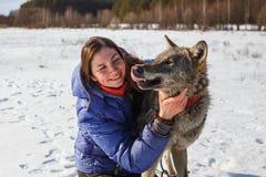 Ritratto di un istruttore della ragazza e di un lupo grigio in un campo nevoso fotografie stock