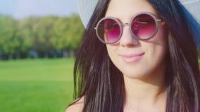 Ritratto di un latino-americano attraente della bruna in occhiali da sole Esamina la macchina fotografica, i giochi del vento con video d archivio