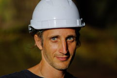 Ritratto di un lavoratore con il casco bianco sulla testa, fondo della natura Fotografia Stock Libera da Diritti