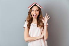 Ritratto di un libro emozionante della tenuta della ragazza sulla sua testa Fotografia Stock Libera da Diritti