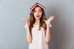 Ritratto di un libro sorpreso della tenuta della ragazza sulla sua testa Immagini Stock