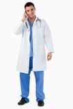 Ritratto di un medico che fa una chiamata di telefono Immagini Stock Libere da Diritti