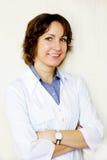Ritratto di un medico femminile contro la parete bianca Immagine Stock
