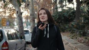 Ritratto di un messaggio di battitura a macchina sorridente della ragazza dei pantaloni a vita bassa sul telefono cellulare mentr archivi video