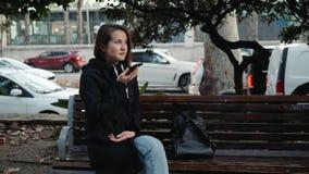 Ritratto di un messaggio di battitura a macchina sorridente della ragazza dei pantaloni a vita bassa sul telefono cellulare mentr stock footage