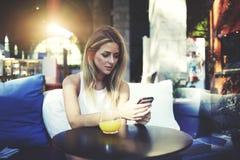 Ritratto di un messaggio grazioso della lettura della donna sul suo telefono delle cellule mentre sedendosi nell'interno moderno  Fotografia Stock Libera da Diritti