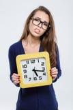 Ritratto di un orologio di parete triste della tenuta della donna Fotografia Stock
