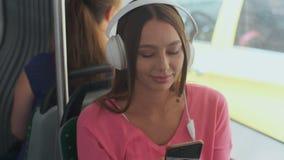 Ritratto di un passeggero della giovane donna che gode del viaggio al trasporto pubblico, sedentesi con le cuffie nel tram modern archivi video
