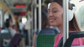 Ritratto di un passeggero della giovane donna che gode del viaggio al trasporto pubblico, sedentesi con le cuffie nel tram modern stock footage