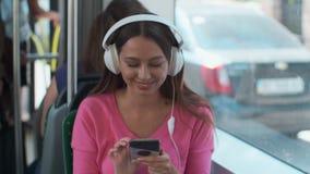 Ritratto di un passeggero della giovane donna che gode del viaggio al trasporto pubblico, sedentesi con le cuffie nel tram modern video d archivio