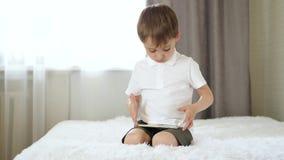 Ritratto di un ragazzino Il bambino si siede sul letto e sui giochi con uno smartphone video d archivio