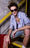 Ritratto di un ragazzo alla moda di distensione sullo stai Immagine Stock Libera da Diritti