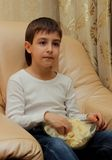 Ritratto di un ragazzo che si siede su una sedia con popcorn Fotografie Stock