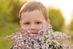 Ritratto di un ragazzo con il lillà mazzo del lillà porpora in mani dei bambini le mani che tengono un lillà porpora fiorisce il  fotografia stock libera da diritti