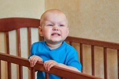Ritratto di un ragazzo divertente che fa smorfie in sua greppia fotografia stock libera da diritti