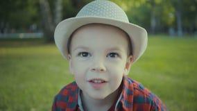 Ritratto di un ragazzo di due anni in un cappello ed in una camicia nel parco stock footage