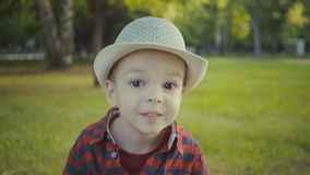 Ritratto di un ragazzo di due anni in un cappello ed in una camicia nel parco archivi video
