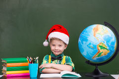 ritratto di un ragazzo felice con il cappello rosso di natale in aula Fotografie Stock
