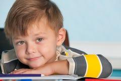 Ritratto di un ragazzo sorridente allo scrittorio Immagini Stock Libere da Diritti