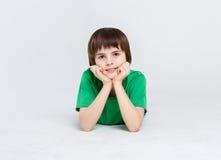 Ritratto di un ragazzo sveglio che si trova sul pavimento su fondo bianco Fotografia Stock