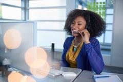 Ritratto di un rappresentante sorridente di servizio di assistenza al cliente con un afro al computer facendo uso della cuffia av Fotografie Stock Libere da Diritti
