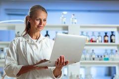 Ritratto di un ricercatore femminile che effettua ricerca in un laboratorio, facendo uso della a Immagini Stock Libere da Diritti