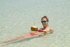 Ritratto di un succo bevente della noce di cocco della donna adorabile nella s Fotografia Stock Libera da Diritti