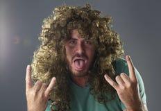 Ritratto di un tipo con una parrucca che fa un simbolo di rock-and-roll Fotografie Stock Libere da Diritti