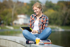 Ritratto di un turco di seduta dello studente al ponte con la compressa Fotografia Stock