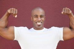 Ritratto di un uomo afroamericano felice che flette i muscoli sopra fondo colorato fotografia stock libera da diritti