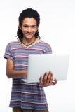 Ritratto di un uomo afroamericano sorridente che per mezzo del computer portatile Fotografie Stock