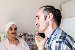 Ritratto di un uomo allegro, bello, caucasico con la barba coperta di stoppie che parla sul telefono cellulare immagini stock libere da diritti