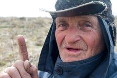 Ritratto di un uomo anziano in vestiti e cappello sudici che hanno alzato il suo dito indice, ho un'idea fotografia stock libera da diritti