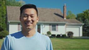 Ritratto di un uomo asiatico felice sui precedenti di nuova casa esaminando la macchina fotografica, sorridente Riuscito acquisto fotografie stock