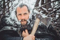 Ritratto di un uomo barbuto con un'ascia in sua mano Uomo barbuto brutale con un'ascia Fotografia Stock Libera da Diritti