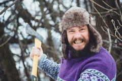 Ritratto di un uomo barbuto con un'ascia in sua mano Uomo barbuto brutale con un'ascia Immagine Stock