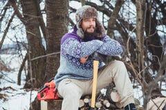Ritratto di un uomo barbuto con un'ascia in sua mano Uomo barbuto brutale con un'ascia Immagine Stock Libera da Diritti