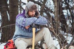 Ritratto di un uomo barbuto con un'ascia in sua mano Uomo barbuto brutale con un'ascia Immagini Stock Libere da Diritti