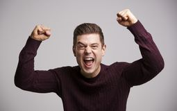 Ritratto di un uomo bianco giovane di celebrazione con le armi su fotografie stock libere da diritti