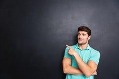 Ritratto di un uomo casuale che indica via sopra il fondo nero Immagini Stock