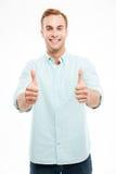 Ritratto di un uomo casuale sorridente che mostra due pollici su Immagine Stock