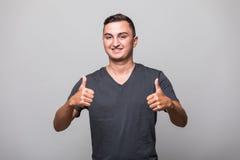 Ritratto di un uomo casuale sorridente che mostra due pollici su e che esamina macchina fotografica Fotografia Stock Libera da Diritti
