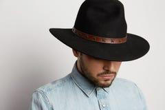 Ritratto di un uomo caucasico pensieroso in camicia d'uso del denim del cappello e di sguardo giù isolato su fondo bianco Immagini Stock Libere da Diritti