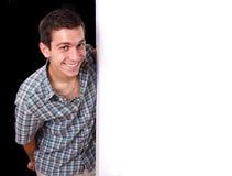 Ritratto di un uomo che dà una occhiata dietro la parete bianca vuota Immagini Stock Libere da Diritti