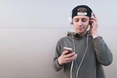 Ritratto di un uomo che sta sui precedenti della parete con un telefono in sue mani e cuffie sulla testa Fotografia Stock Libera da Diritti