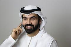 Ritratto di un uomo d'affari arabo Speaking In Phone che sorride affrontando la macchina fotografica fiero e portando il vestito  immagini stock